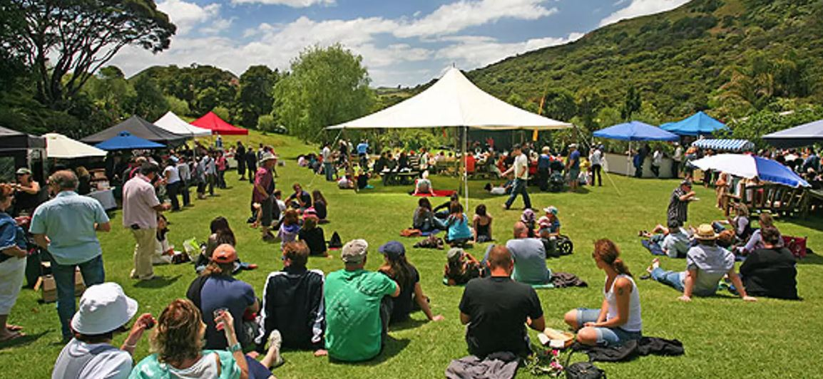 People sitting on the Grass and under sun umbrellas watching the musicians play at the Waiheke Island Jazz Festival