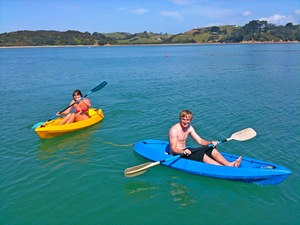 Teenagers kayaking in the sunny bay on Waiheke Island