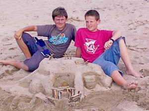 Two boys proudly sitting beside their amazing sand castle on Waiheke Island