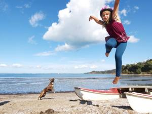 Child at beach leaping into the air off a small boat at Waiheke Island