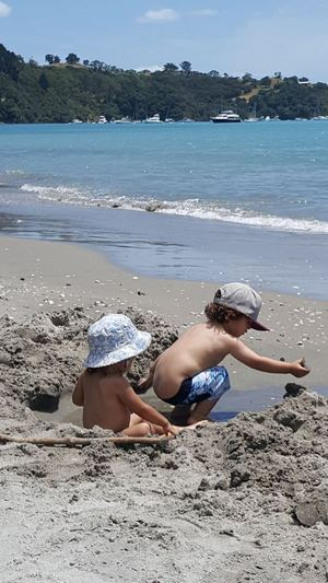 Two small children playing in the water on the sand by the sea at Waiheke Island